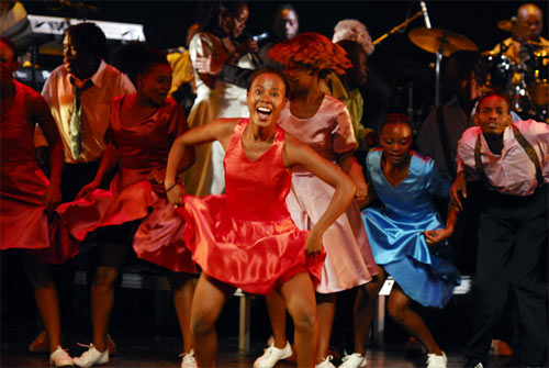 vrolijk meisje danst in rood jurkje